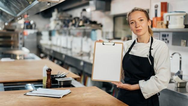 Вид спереди женского шеф-повара, держащего буфер обмена на кухне