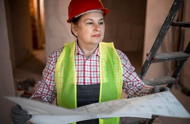 청사진으로 여성 건설 노동자의 전면보기
