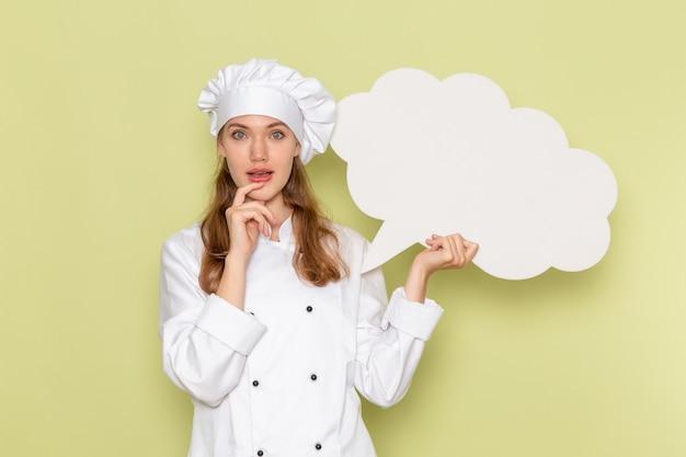 緑の壁に白い看板を保持している白いクックスーツの女性料理人の正面図