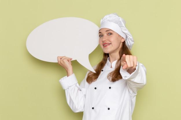 緑の壁に大きな白い看板を保持している白いクックスーツの女性料理人の正面図