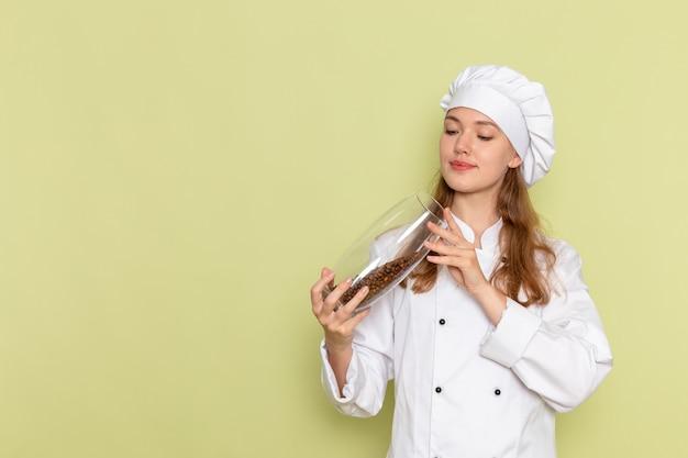 緑の机の上のコーヒーの種でいっぱいの缶を保持している白いクックスーツの女性料理人の正面図キッチン料理料理食事女性の色