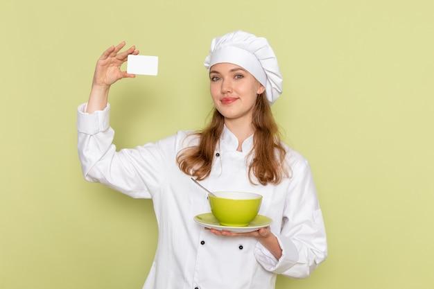 Вид спереди повара в белом костюме повара, держащего карточку и тарелку на зеленой стене