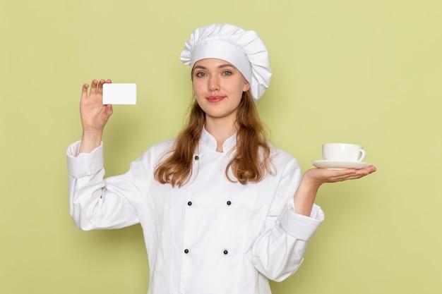 Вид спереди женщины-повара в белом костюме повара, держащего чашку и карточку на зеленой стене
