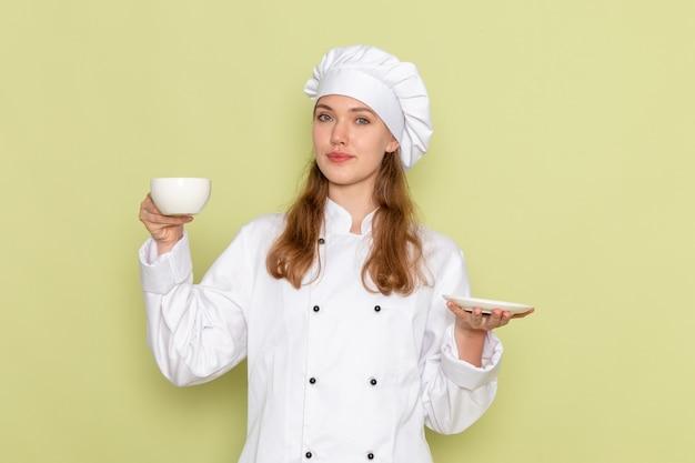 Вид спереди повара в белом костюме повара, держащего чашку и тарелку на зеленой стене