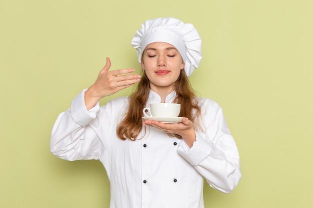 一杯のコーヒーを保持し、緑の壁ににおいがする白いクックスーツの女性料理人の正面