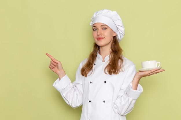 一杯のコーヒーを保持し、緑の机の上で笑っている白いクックスーツの女性料理人の正面図キッチン料理料理食事女性の色