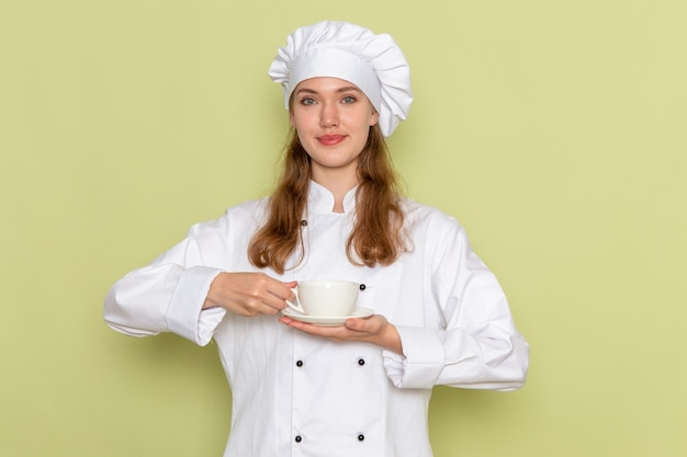Вид спереди повара в белом костюме повара, держащего чашку на зеленой стене