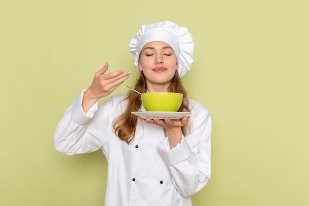 緑のプレートを保持し、緑の壁ににおいがする白いクックスーツの女性料理人の正面図