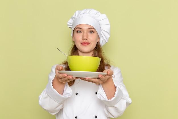 緑のプレートを保持し、緑の壁に笑みを浮かべて白いクックスーツの女性料理人の正面図