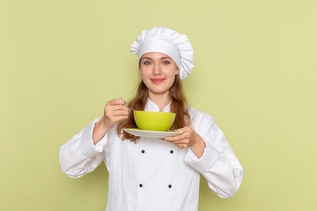 緑の壁に緑のプレートを保持している白いクックスーツの女性料理人の正面図