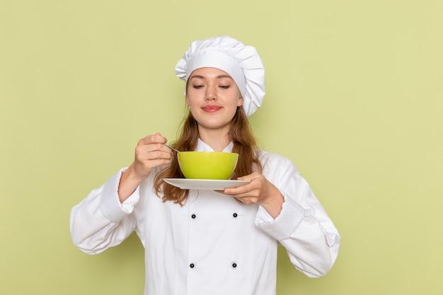 緑の机の上の皿と緑のプレートを保持している白いクックスーツの女性料理人の正面図キッチン料理料理料理食事女性