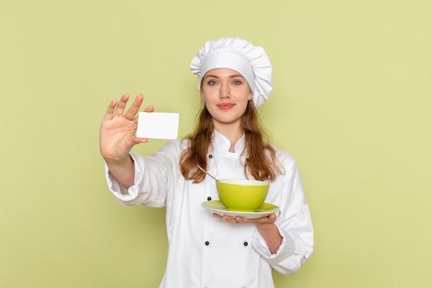 緑の壁にプレートとカードを保持している白いクックスーツの女性料理人の正面図