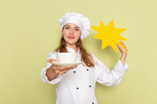 緑の壁に黄色の看板とプレートを保持している白いクックスーツの女性料理人の正面図