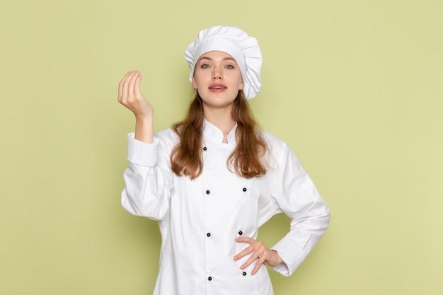 緑の壁にポーズをとって白いクックスーツの女性料理人の正面図