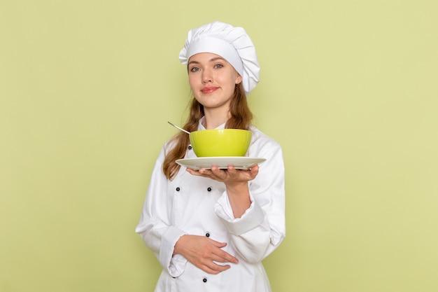 緑の壁に緑のプレートを保持して笑っている白いクックスーツの女性料理人の正面図