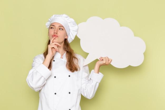緑の壁に白い看板を考えて保持している白いクックスーツの女性料理人の正面図