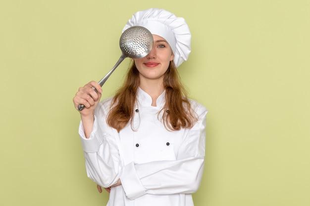 大きな銀のスプーンを保持し、緑の壁に笑顔で考えている白いクックスーツを着ている女性料理人の正面図
