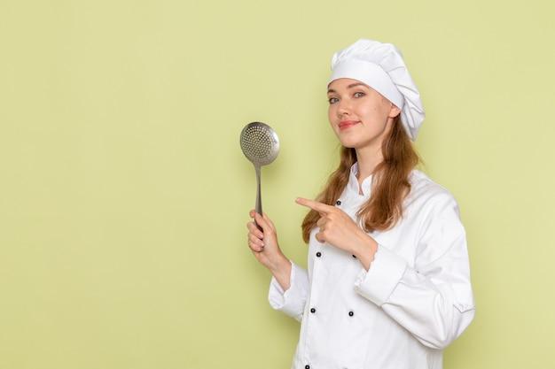 緑の壁に大きな銀のスプーンを保持している白いクックスーツを着ている女性料理人の正面図