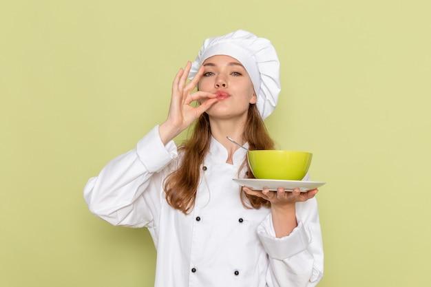 Вид спереди женщины-повара в белом костюме повара, держащей зеленую тарелку с супом на зеленой стене