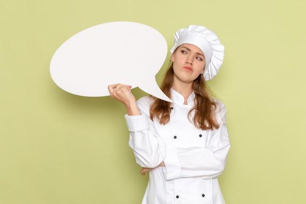 Вид спереди женщины-повара в белом костюме повара, держащего белый знак и думающего на светло-зеленой стене