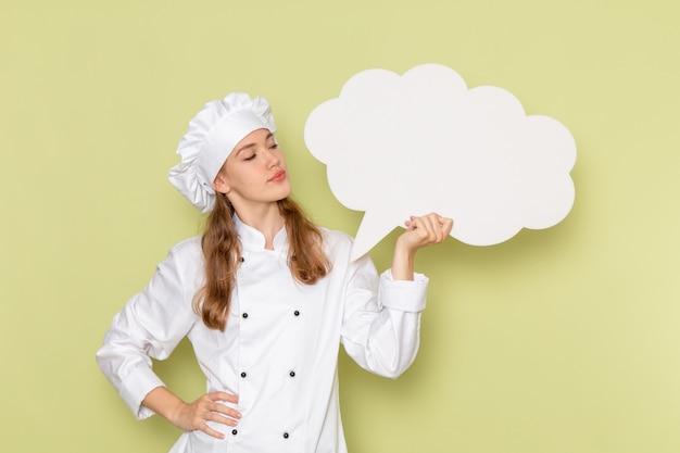 緑の壁に白い看板を保持している白いクックスーツを着ている女性料理人の正面図