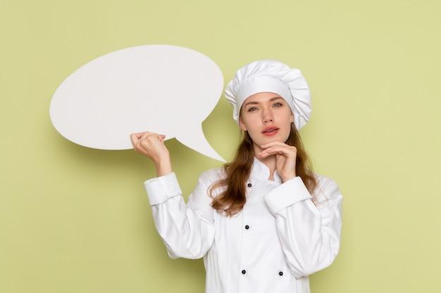緑の壁に考えている白い看板を保持している白いクックスーツを着ている女性料理人の正面図