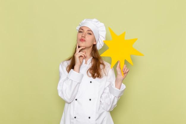 Вид спереди женщины-повара в белом костюме повара с желтым знаком на зеленой стене