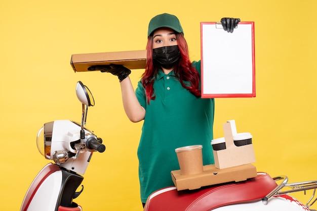 黄色の壁に配達コーヒーと食べ物とマスクで女性の宅配便の正面図
