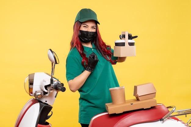 Вид спереди курьера-женщины в маске с доставкой кофе и еды на желтой стене