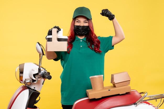 黄色の壁に配達コーヒーとマスクの女性宅配便の正面図