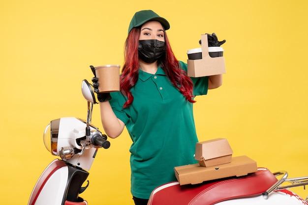 Вид спереди курьера-женщины в маске с доставкой кофе на желтой стене