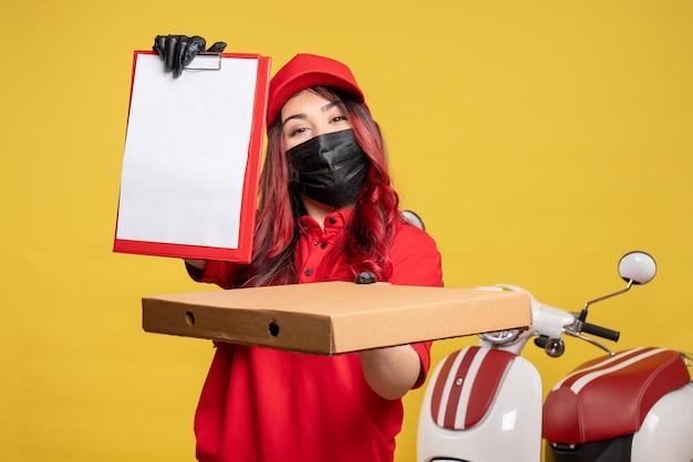 Вид спереди курьера-женщины в маске с коробкой для еды и запиской на желтой стене