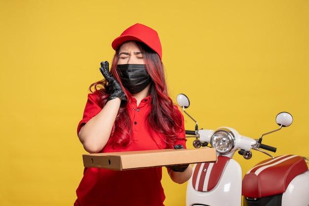 Вид спереди курьера-женщины в маске с коробкой для доставки еды на желтой стене
