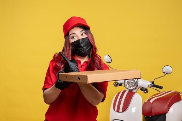 黄色の壁に配達フードボックスとマスクで女性の宅配便の正面図