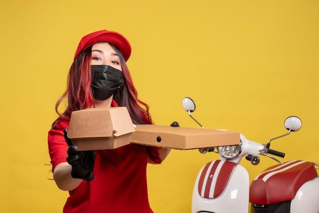 Вид спереди курьера-женщины в маске с доставкой еды на желтой стене