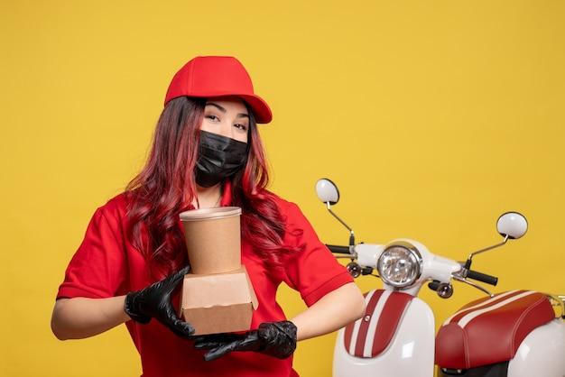 黄色の壁に配達食品とマスクで女性の宅配便の正面図