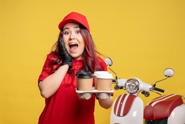 Вид спереди курьера-женщины в красной форме с кофе на желтой стене