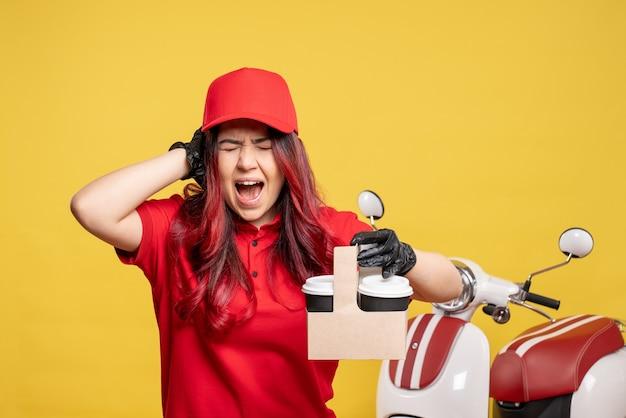 黄色の壁にコーヒーと赤い制服を着た女性の宅配便の正面図