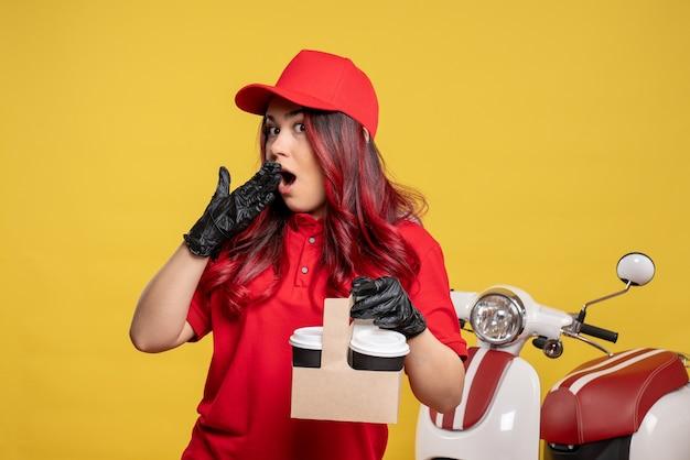 노란색 벽에 커피와 함께 빨간색 유니폼 여성 택배의 전면보기