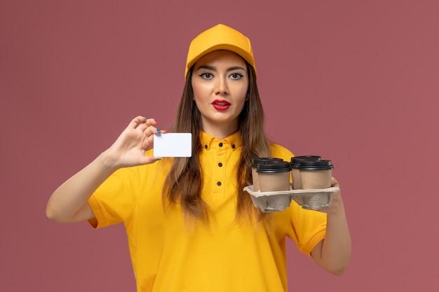 ピンクの壁に茶色のコーヒーカップとカードを保持している黄色の制服と帽子の女性の宅配便の正面図