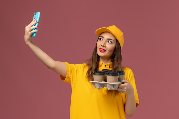 黄色の制服と茶色のコーヒーカップを保持し、ピンクの壁に自分撮りをしているキャップの女性の宅配便の正面図