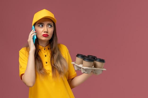 黄色の制服と茶色のコーヒーカップを保持し、ピンクの壁に電話で話しているキャップの女性の宅配便の正面図