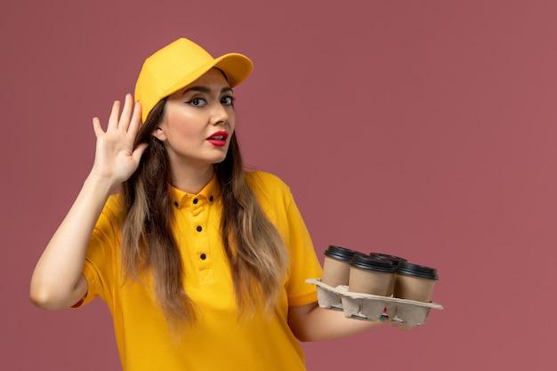 黄色の制服と茶色の配達コーヒーカップを保持し、ピンクの壁で聞くことを試みているキャップの女性の宅配便の正面図