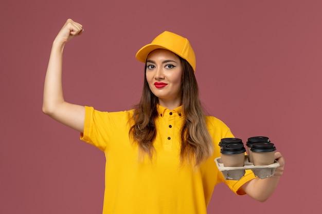 ピンクの壁に曲がる茶色の配達コーヒーカップを保持している黄色の制服と帽子の女性の宅配便の正面図
