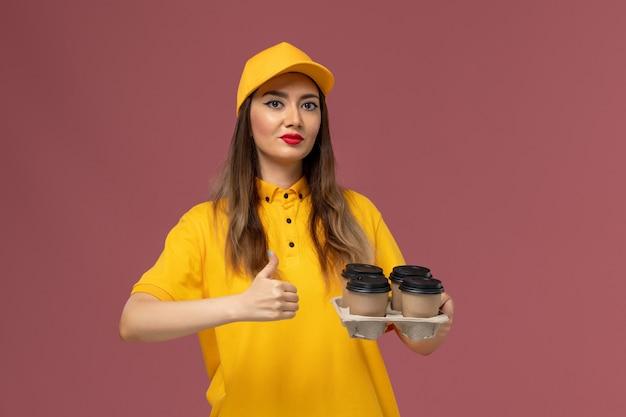 ピンクの壁に茶色の配達コーヒーカップを保持している黄色の制服と帽子の女性の宅配便の正面図