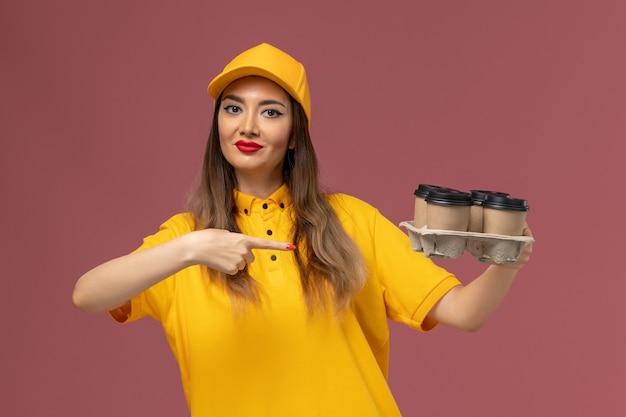 Вид спереди курьера-женщины в желтой форме и кепке, держащего коричневые кофейные чашки на розовой стене