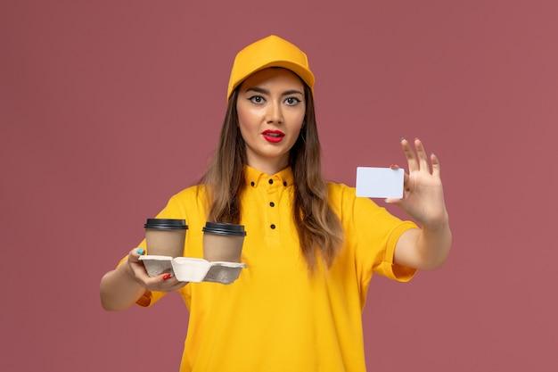 Вид спереди курьера-женщины в желтой форме и кепке, держащей кофейные чашки и открытку на розовой стене