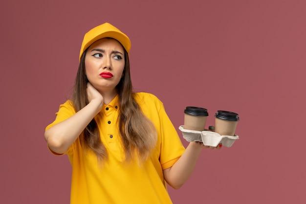 Вид спереди курьера-женщины в желтой униформе и кепке с доставкой кофейных чашек с болью в шее на розовой стене