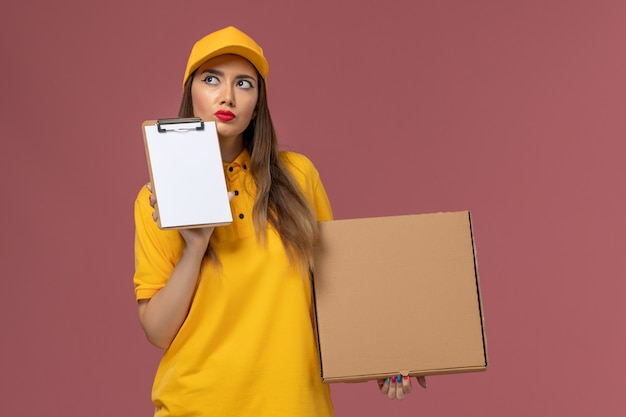 ピンクの壁に考えている黄色の制服とキャップ保持フードボックスとメモ帳の女性の宅配便の正面図