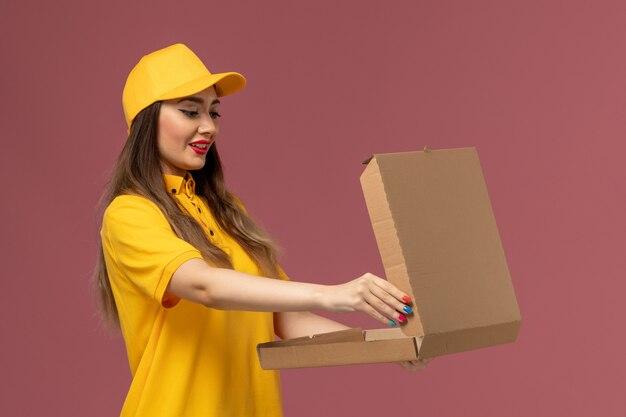 黄色の制服と淡いピンクの壁にフードボックスを保持しているキャップの女性の宅配便の正面図